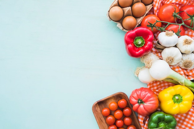 Eggs and healthy vegetables on blue colored background