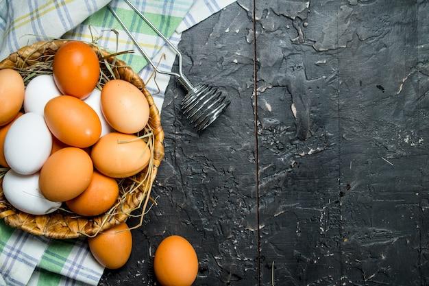 泡立て器とナプキンが入ったバスケットに入った卵。黒の素朴な背景に。