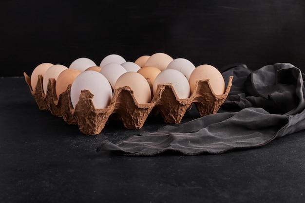 Яйца в картонной таре на черной поверхности.