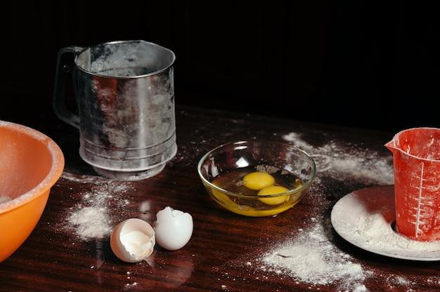 Яйца в стеклянной миске на кухонном столе в процессе приготовления теста крупным планом