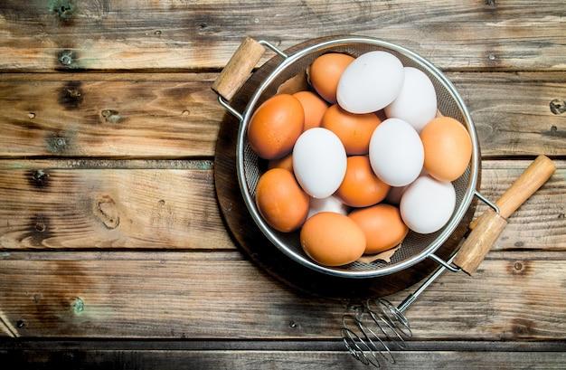 泡だて器で鍋に卵。木製の背景に。