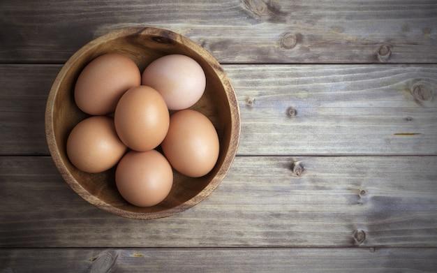 木製のテーブルに木製のボウルに卵