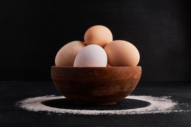 Яйца в деревянной чашке на черном пространстве.