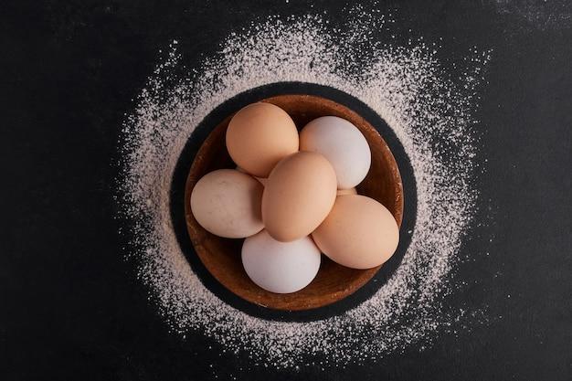 黒い表面、上面図の木製カップの卵。