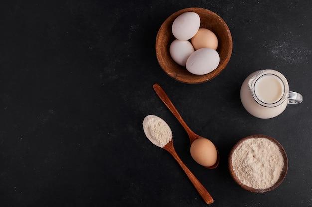 Яйца в деревянной чашке с ложкой муки и банке молока, вид сверху.