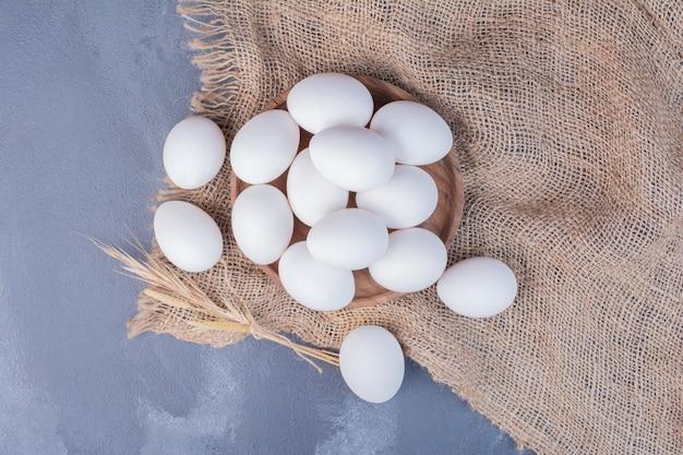 黄麻布の上の木製の大皿の卵