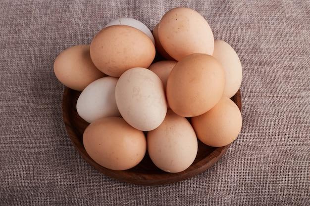 キッチンタオルの上の木製の大皿に卵、上面図。
