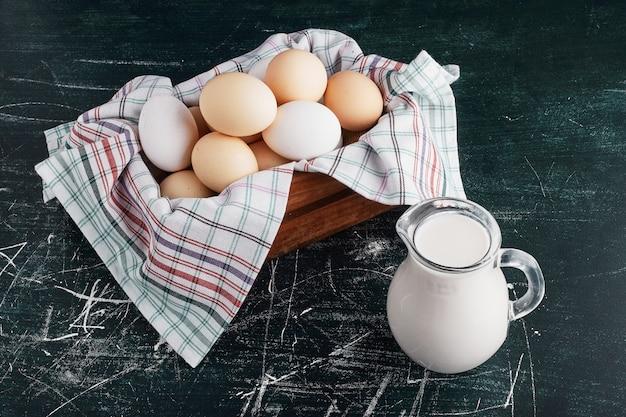 牛乳の瓶が周りにある木製トレイの卵。