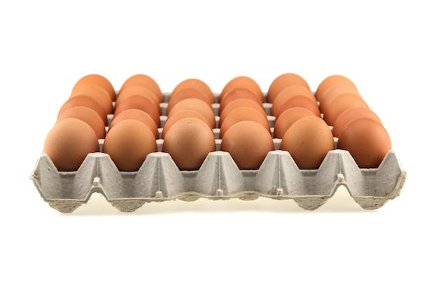 カートンボックスの卵。白い背景で隔離のパッケージに茶色の新鮮な30個の鶏卵を閉じます。