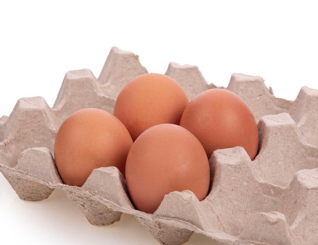 Яйца в пакете лотка для бумаги отсек на белом фоне