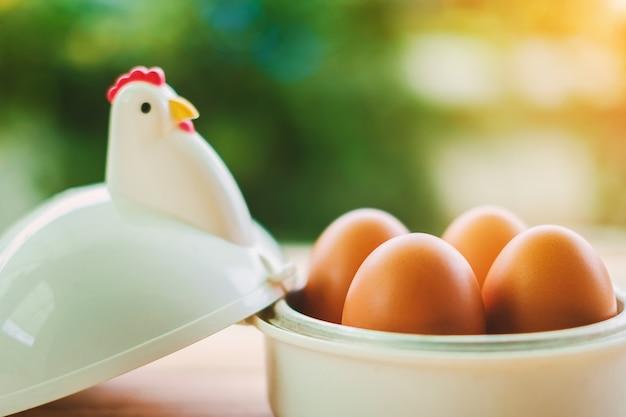 Яйца в яичной чашке на завтрак с размытым зеленым фоном