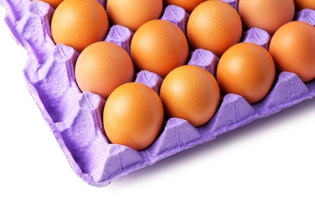 Яйца в лотке для бумаги на белом фоне