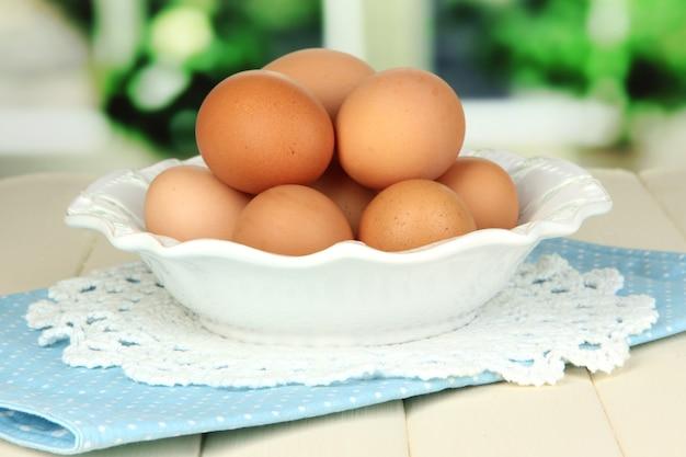 Яйца в тарелке на деревянном столе на поверхности окна