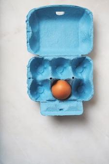 파란 계란 상자에있는 계란. 미니멀리스트 음식 개념. 플랫 레이. 평면도.