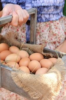 屋外の女性の手で木製のバスケットに卵