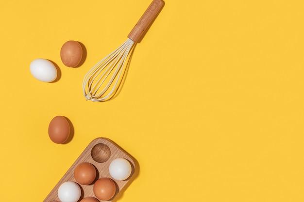 Яйца в деревянной коробке для яиц и венчик на желтом фоне. плоская планировка вид сверху копирование пространства.