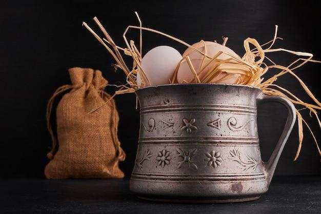 乾いた草の中の金属製の鍋の中の卵。
