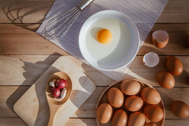 Eggs lay on wooden trays and have broken eggs.