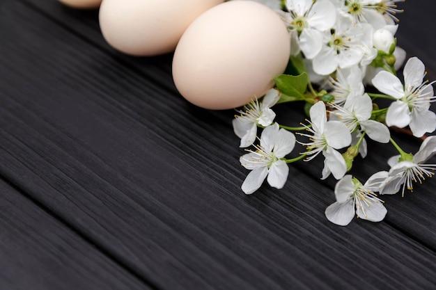 花の枝で自然な卵。イースターホリデー。桜の花とスタイリッシュな無着色のイースターエッグは、柔らかな光の中で暗い木製の背景に枝分かれします。テキスト、上面図、フラットレイ用のコピースペース