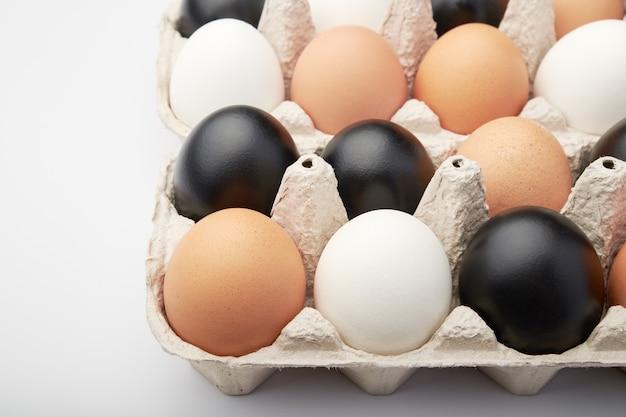 段ボール箱のさまざまな色の卵。黒、白、茶色の鶏の卵。