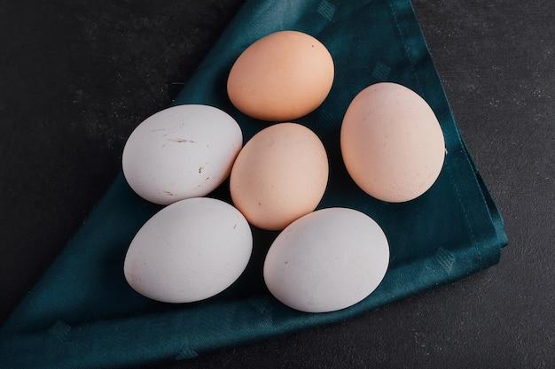 黒い表面の緑のテーブルクロスの上の卵、上面図。