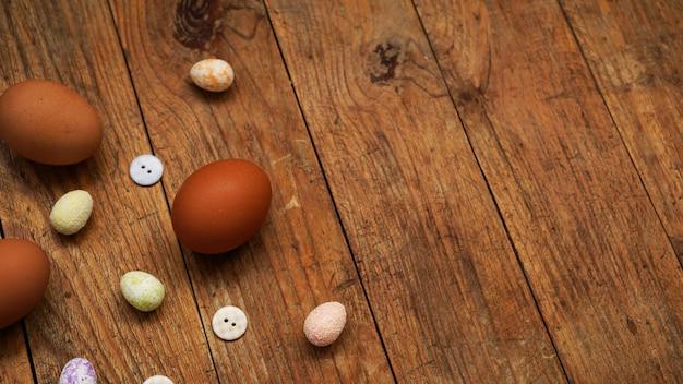 テキスト用のコピースペースがある木製の素朴な表面の卵。イースターデコレーション用の新鮮な鶏卵と装飾卵。