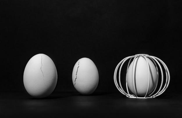 Яйца на черном фоне в одной клетке