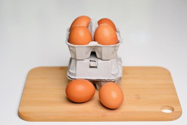 Яйца на разделочной доске и много свежих сырых коричневых куриных яиц