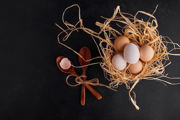 Яйца на сушеной траве на черном пространстве.