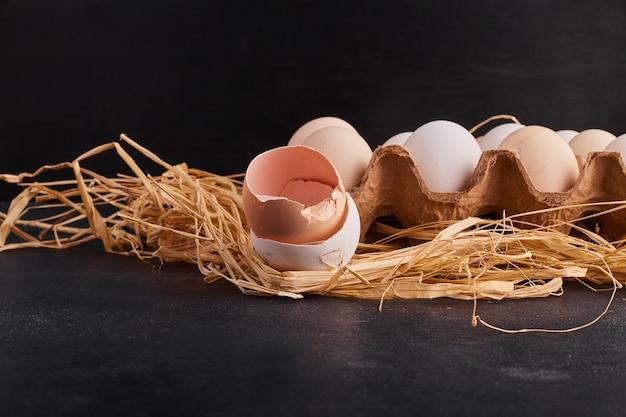 Яйца на сухой траве и в картонном лотке.