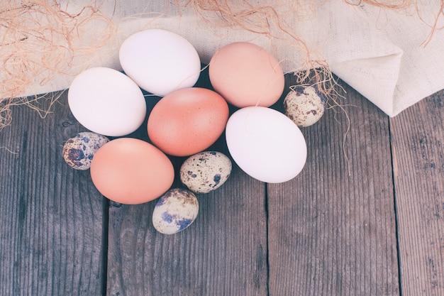 Яйца на текстильной скатерти над деревенским деревянным столом с copyspace