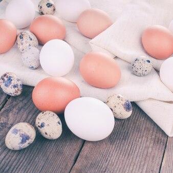 Яйца на текстильной скатерти над деревенским деревянным столом