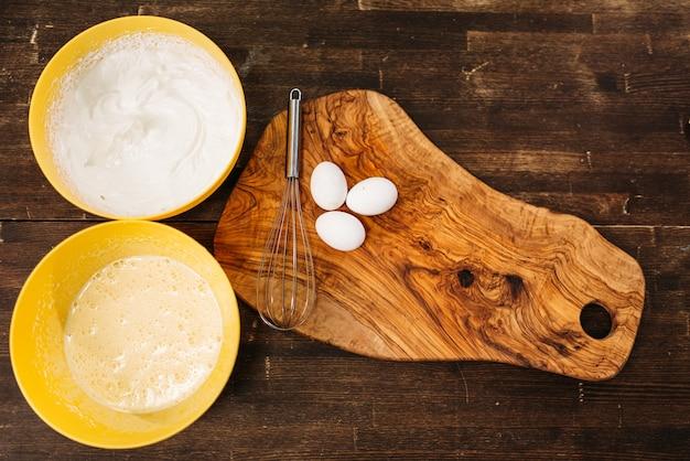 Яйца на деревянной разделочной доске против мисок с видом сверху ингредиентов торта. концепция приготовления домашней пищи.