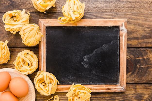 Eggs and pasta near blackboard