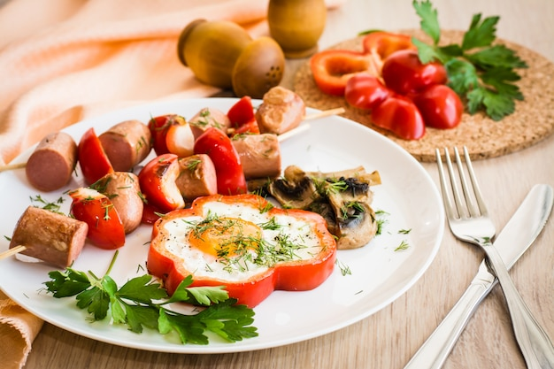 Eggs in peppers, mushrooms and sausage with peppers on skewers