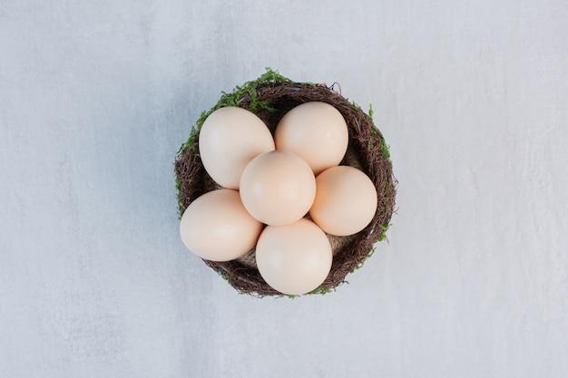 Яйца сложены в причудливой миске на мраморном столе.