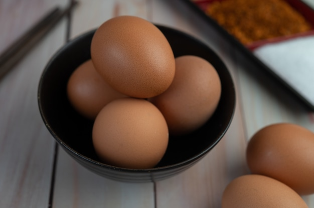 Eggs placed in a cup on a wooden floor.