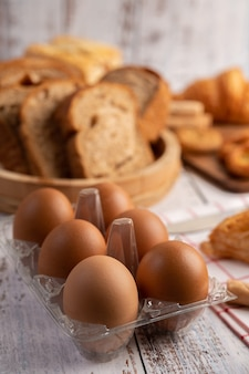 Eggs in a plastic panels and bread that is placed on a white wooden plate.