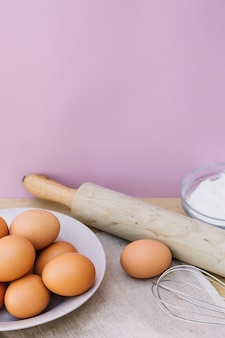 Eggs on plate; rolling pin; whisk and flour on desk against pink background