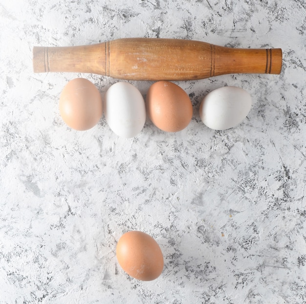 Eggs, rolling pin on white concrete surface