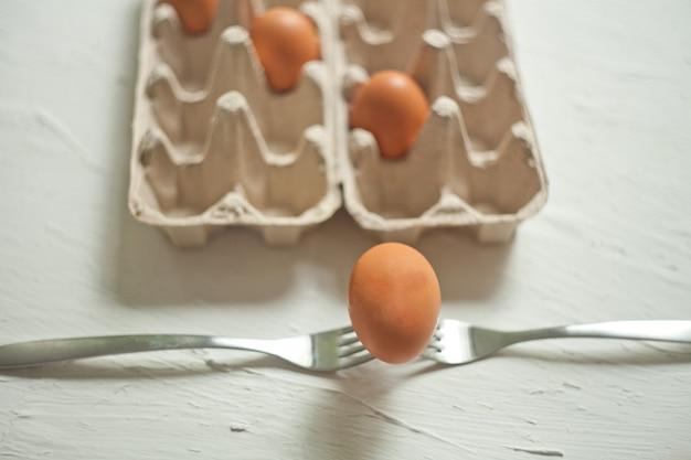 フォークでオムレツを調理するための卵殻。白い背景の上の黄色い卵。材料