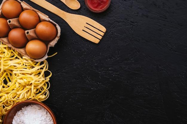 Eggs and spatula near pasta and flour