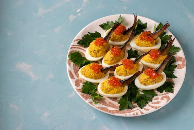 계란 sprats와 파란색 배경에 접시에 빨간 캐 비어와 박제.