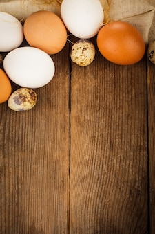 Eggs on textile tablecloth over rustic wooden table with copyspace