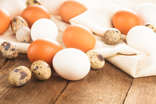 Eggs on textile tablecloth over rustic wooden table