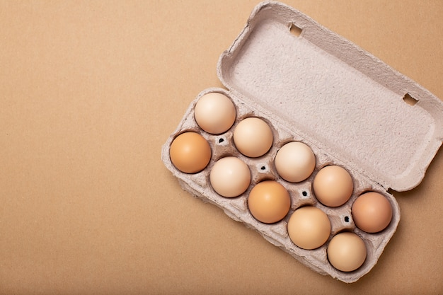 Eggs tray on brown background, copy space, top view.