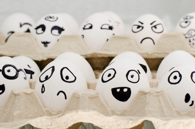 Eggs in tray painted with different emotions: sadness, surprise, amazement. close-up