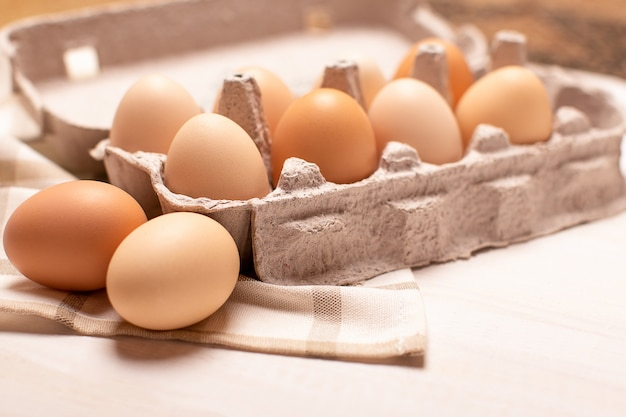 Eggs tray on white table, eggs with selective focus, close up