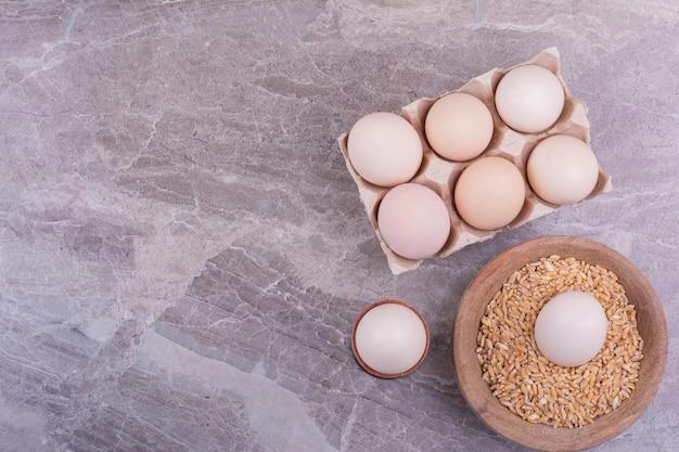 Uova in una tazza di grano e sul vassoio di cartone.