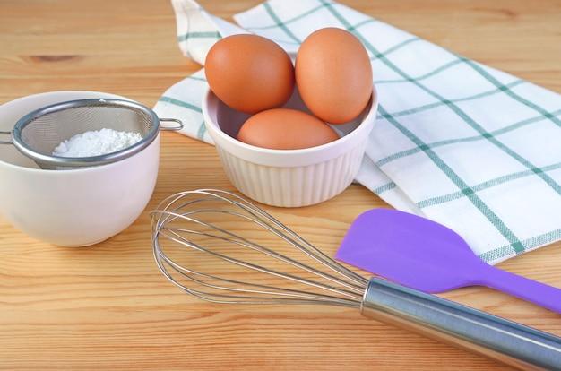 Яйца, венчик и кухонная утварь на деревянной поверхности